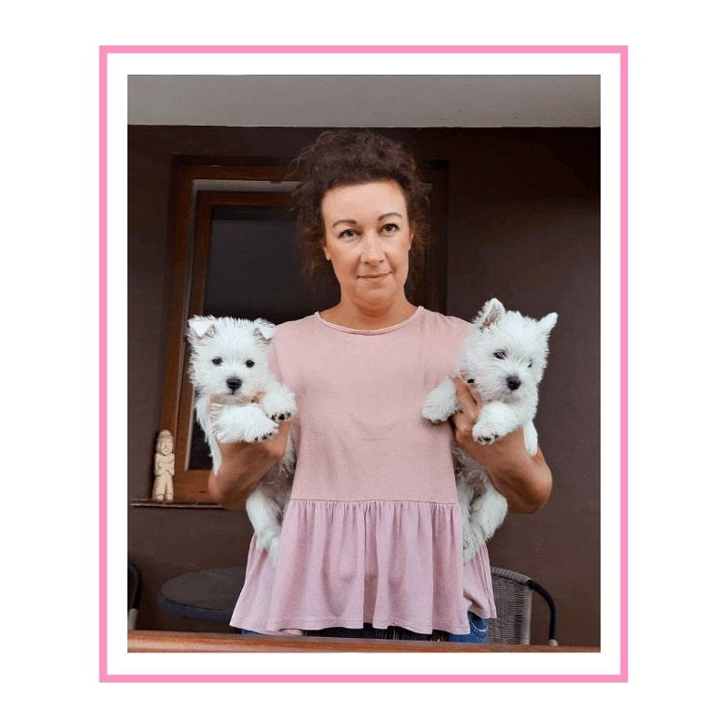 Brązowo-włosa kobieta w różowej koszulce, trzymająca dwa białe szczeniaki
