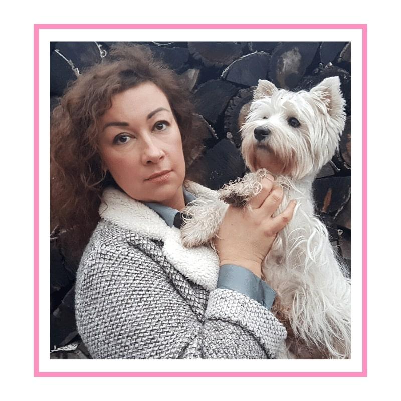 Brązowo-włosa kobieta trzymająca na rękach psa rasy West Highland white terrier